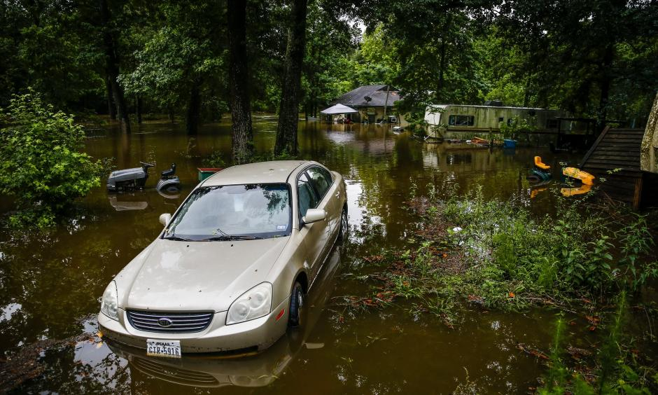 A car and home sit in floodwater from Spring Creek along North Ravenswood Drive on Friday in Magnolia, Texas. Photo: Michael Ciaglo, AP