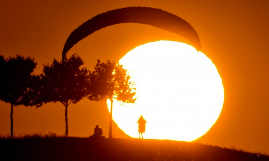 Germany set a new all-time record high temperature on Sunday. Here, a paraglider lands at sunset in Kronsberg amid the heat on Wednesday. Photo: JULIAN STRATENSHULTE