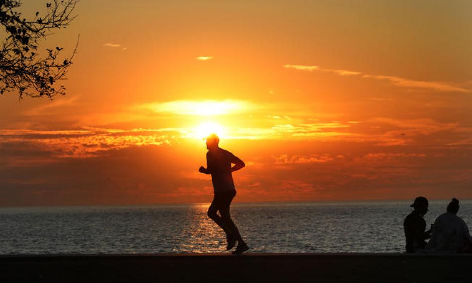 A hot yellow sun rises on Lake Michigan at Montrose Avenue Monday Sept. 25, 2017 as a jogger takes advantage of the cool early morning temperatures. Although still cool at sunrise another record-breaking hot day was expected for the Chicago area.  Photo: Nancy Stone / Chicago Tribune