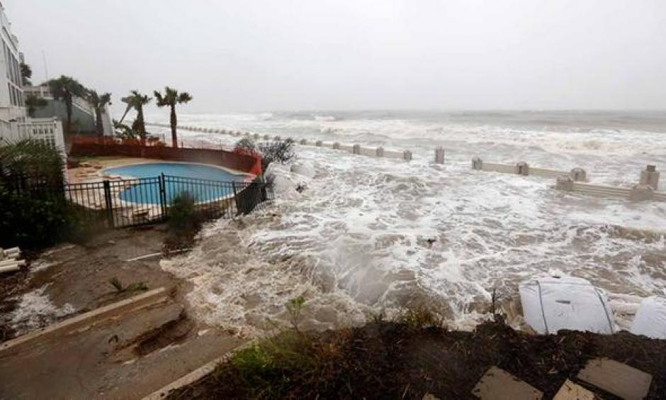 Waves crash over an experimental sea wall to protect homes during high tide on the Isle of Palms. Photo: AP