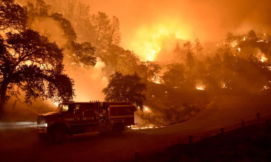 A Cal Fire truck is driven away from flames as the Rocky Fire burns near Clearlake, California, on August 2, 2015. Photo: Josh Edelson / AFP / Getty