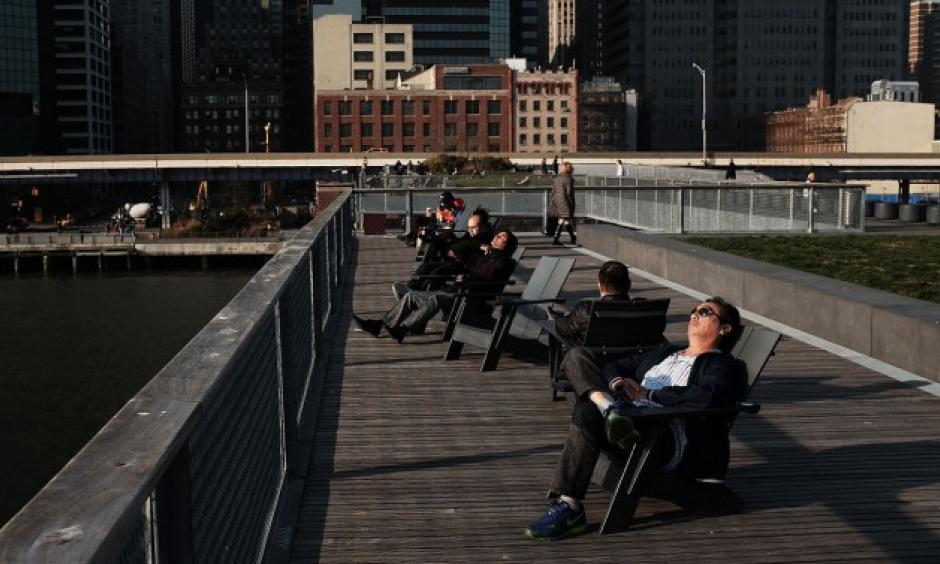 People enjoy unseasonably warm weather in lower Manhattan in December. Photo: Getty
