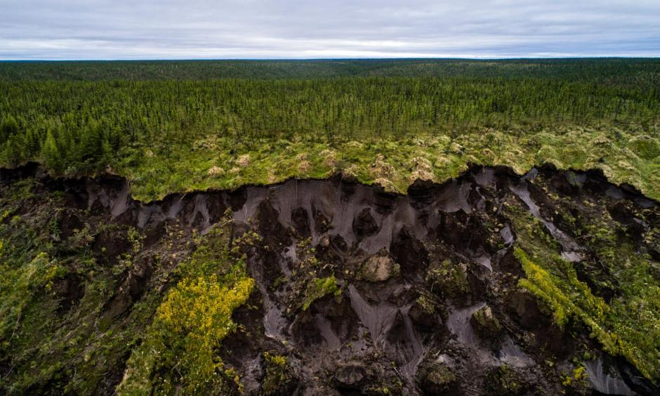 Ground collapses at Duvanny Yar, a permafrost megaslump along the Kolyma River in northern Siberia. New research suggests that some land in Arctic Alaska and Russia may no longer freeze at all. This constantly moving landslide, driven by erosion and sped up by warming temperatures, is an important research site for scientists, who use it to track what happens as carbon-rich land that has been frozen for centuries begins to thaw. Photo: Katie Orlinsky, National Geographic