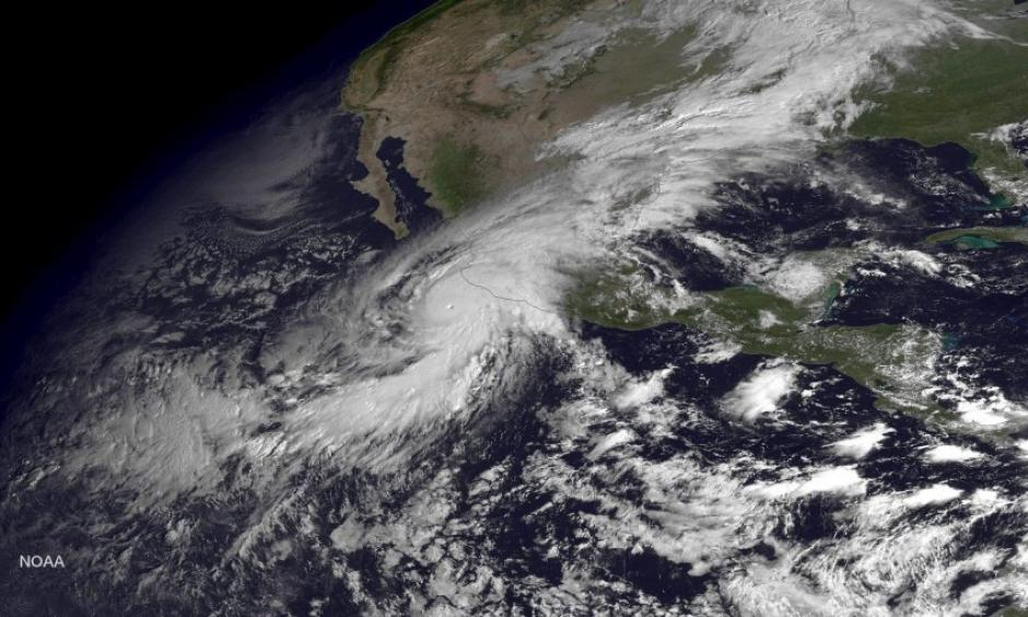 A handout satellite image made at 10:45 am ET and released by the US National Oceanic and Atmospheric Administration (NOAA) on 23 Oct. 2015 shows Hurricane Patricia (L) as it approaches the coastline of Mexico from the Eastern Pacific. Image: EPA / NOAA / HANDOUT