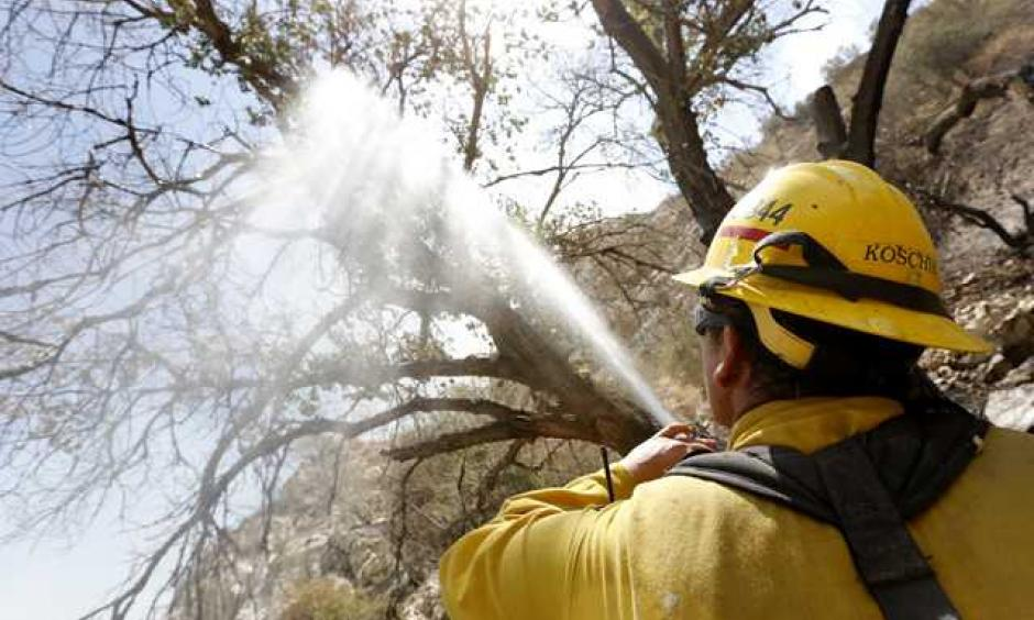 Jake Koschik of Mendocino sprays down hot spots on a tree off Soledad Canyon Road and Agua Dulce Canyon Road in Acton as multiple fire agencies work on a controlled burn in the area on Tuesday. Photo: Katharine Lotze