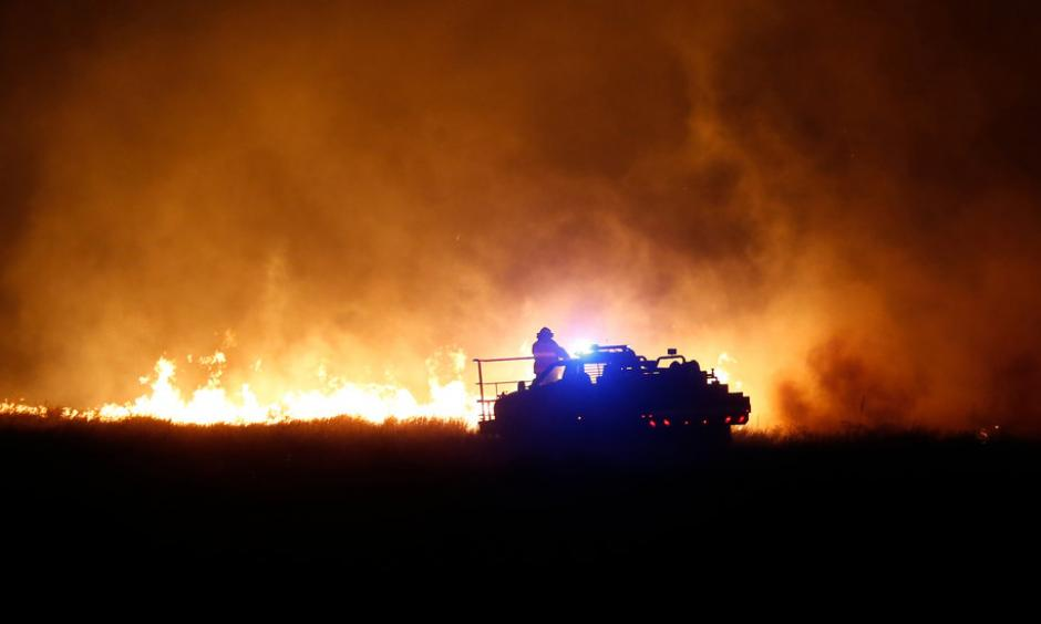 Firefighters near Protection, Kan., this week. Dry conditions have helped fuel the flames. Photo: Credit Bo Rader, The Wichita Eagle, via Associated Press