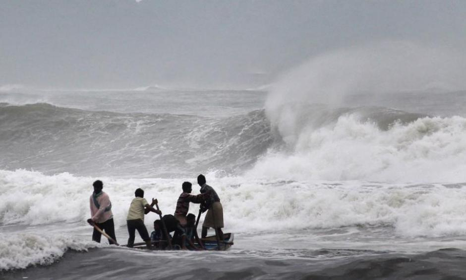 Indian fishermen negotiate their skiff through rough waves ahead of Cyclone Hudhud. Photo: STRDEL/AFP/Getty