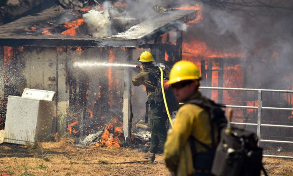 Firefighters battle flames as a house burns in Lower Lake, Calif., in August 2016. Photo: Josh Edelson, AP