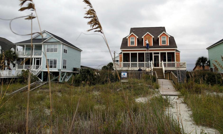 Workers install window shutters at an oceanfront home in anticipation of Hurricane Matthew in Garden City Beach, S.C., U.S. Oct. 5, 2016. Photo: Randall Hill