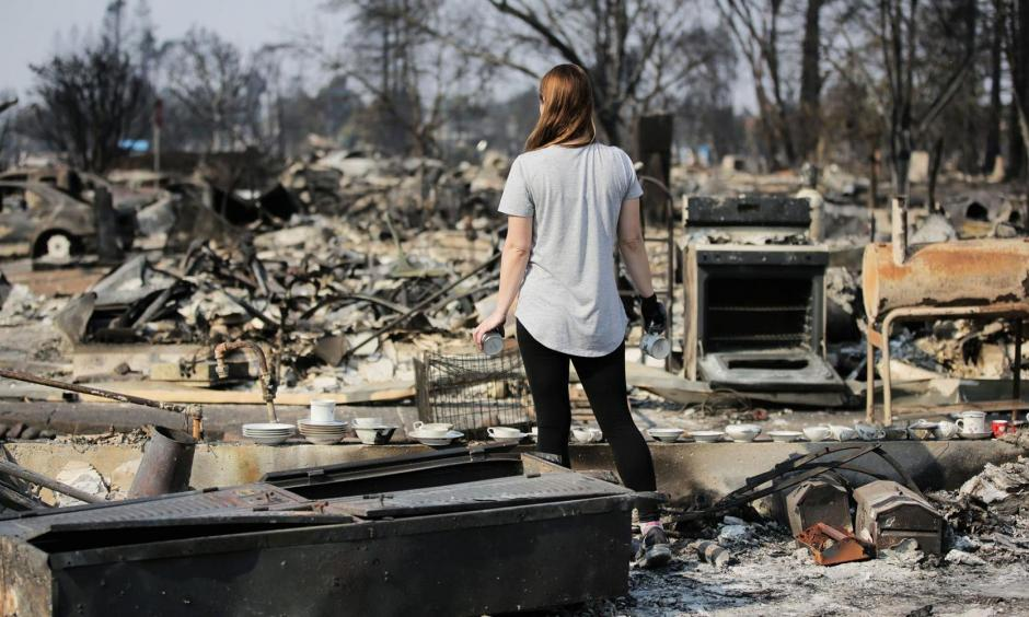 A woman looks out at the destruction caused by the Tubbs fire while holding items of emotional importance salvaged from her childhood home in the Coffey Park neighborhood on October 15, 2017 in Santa Rosa, California. Photo: Getty Images