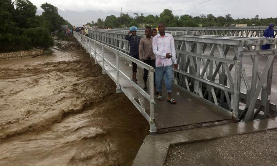 Floodwaters from Hurricane Matthew rage down a river as people cross a bridge in Port-au-Prince, Haiti. Photo: Carlos Garcia Rawlins, Reuters