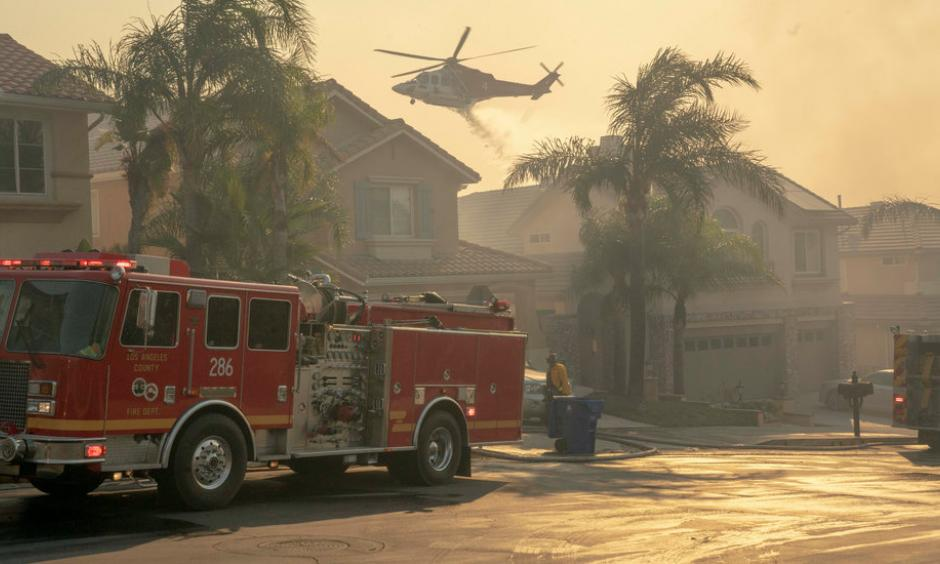 A helicopter dropped water onto a burning hillside in the Porter Ranch neighborhood. Credit: Kyle Grillot, The New York Times