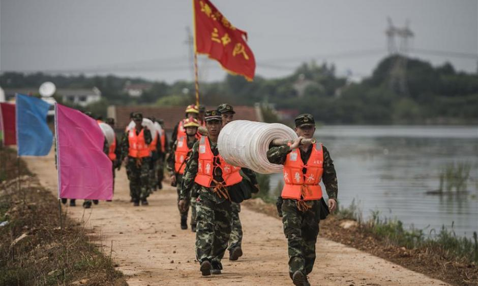 Armed police soldiers prepare for the breach of the embankment on the dike of Niushan Lake in central China's Hubei Province, July 13, 2016. The Hubei provincial government Tuesday decided to break the embankment between Liangzi Lake and Niushan Lake, to prevent possible flood overflow over the dike. The operation will be executed on July 14. Photo: Xiao Yijiu, Xinhua
