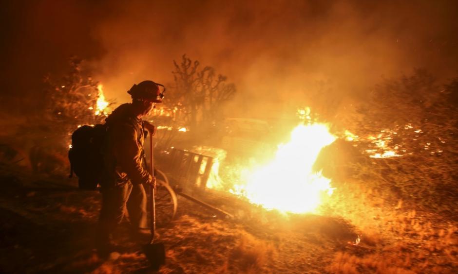 A firefighter watches the Blue Cut wildfire burning near Cajon Pass, north of San Bernardino, California on August 16, 2016. Photo: Ringo Chiu, AFP, Getty