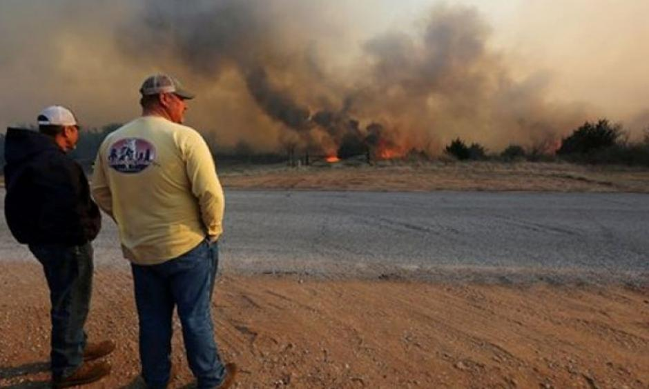Jeff Clark and Roger Van Rankin watch the fire east of Lake City, Kan., Wednesday, March 23, 2016. Photo: AP