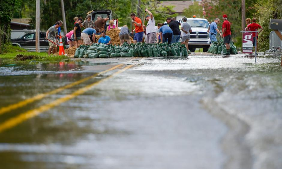Volunteers pitched in to help residents fill sand bags against flooding from the Vermilion River in Lafayette, La., on Monday. Photo: Scott Clause/The Daily Advertiser, via Associated Press