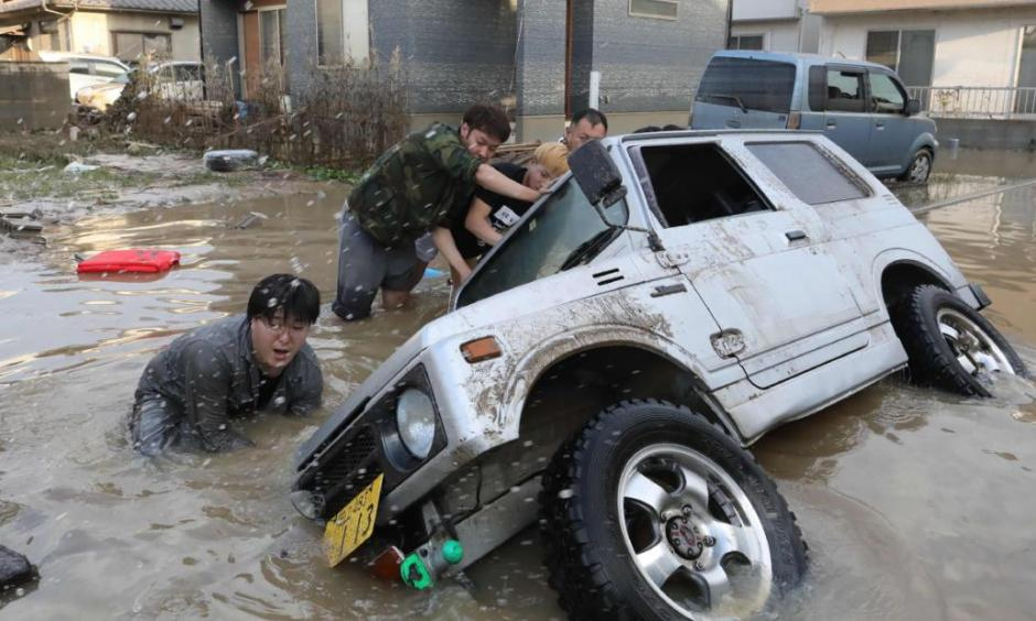 Residents try to upright a vehicle stuck in a flood hit area in Kurashiki, Okayama prefecture on July 9, 2018. Credit: CNN