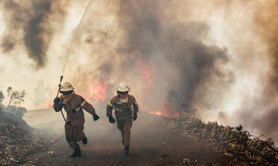 Flames and smoke cut off roads on Sunday in Capela Sao Neitel, in central Portugal, where members of the National Guard tried to contain several forest fires. Photo: Paulo Cunha, European Pressphoto Agency