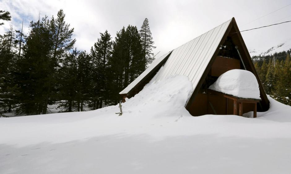 An above-average amount of snow covers a small cabin in Phillips, Calif., Dec. 30, 2015. Photo: Fred Greaves, Reuters