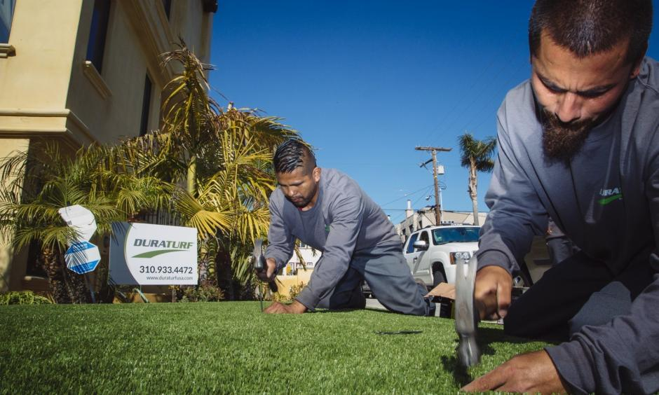 Workers from DuraTurf work on final touches with the artificial lawn at the home of Christopher Knight, who had the turf installed because of California's drought. Photo: David Walter Banks, Washington Post