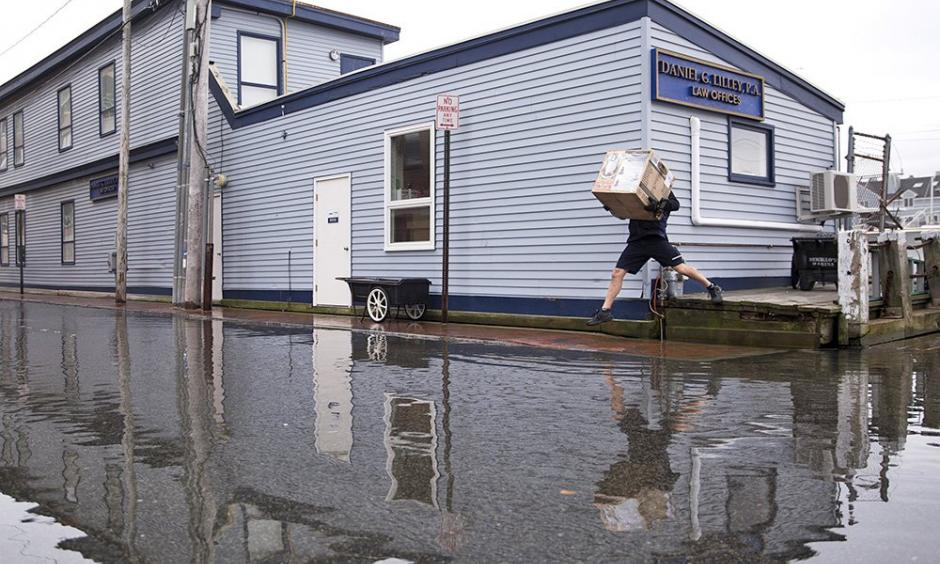 A FedEx delivery man jumps over pooling water on Portland Pier during the king tide. Tides are caused by the gravitational pull of the moon and this week's supermoon was closer to Earth than it has been in 68 years. Photo: Brianna Soukup