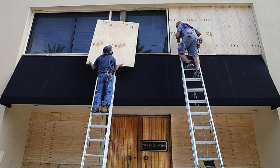 Workers Victor Briones and Dennis Flores board up the Haggard Law offices windows in Coral Gables on September 07, 2017 as South Florida prepares for the coming hurricane Irma. Photo: Pedro Portal