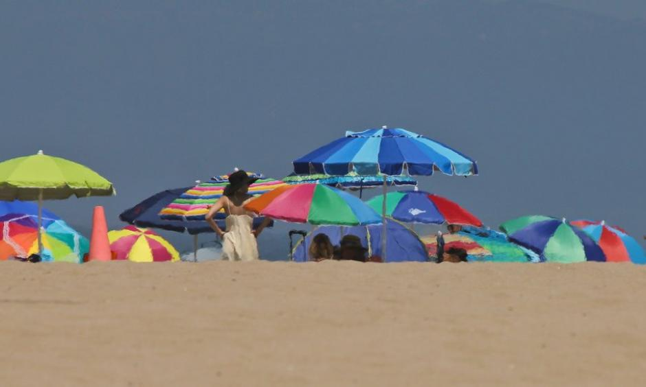 Beachgoers camped out under umbrellas at Manhattan beach this summer. A heat wave is expected to push Southern California temperatures into the triple digits. Photo: John Antczak, Associated Press