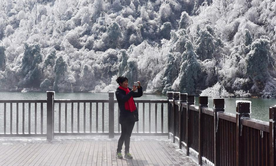 A woman photographs the scene at Hangzhou, in eastern China's Zhejiang province. In Inner Mongolia, the temperature fell to a record low of -46.8C (-52F). Photo: AFP, Getty