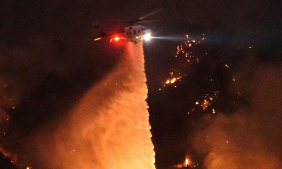 Thousands have been forced to evacuate their homes as a wildfire threatens the Santa Clarita Valley, north of Los Angeles. A resident describes being evacuated as firefighters worked to save his neighborhood. Photo by Ringo H.W. Chiu/Associated Press.
