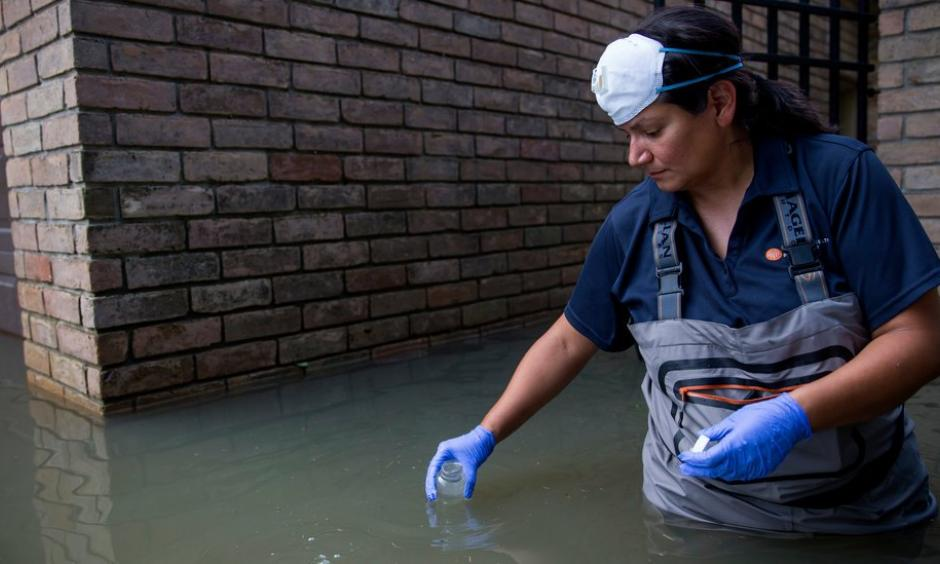 A woman collected water samples in September in a Houston neighborhood affected by flooding from Hurricane Harvey. Photo: Eric Thayer for The New York Times