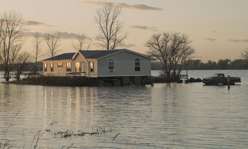 A home is surrounded by floodwaters in Bartlett, Iowa. Credit: Nati HarnikAP