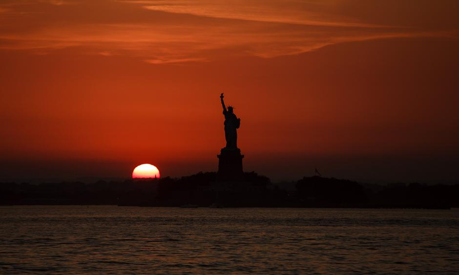 In this July 1, 2018 file photo, the sun sets behind the Statue of Liberty in New York as record high temperatures were recorded over the week in the U.S. and elsewhere. An AP data analysis of records from 1999-2019 shows that in weather stations across America, hot records are being set twice as often as cold ones. Photo: Andres Kudacki, AP