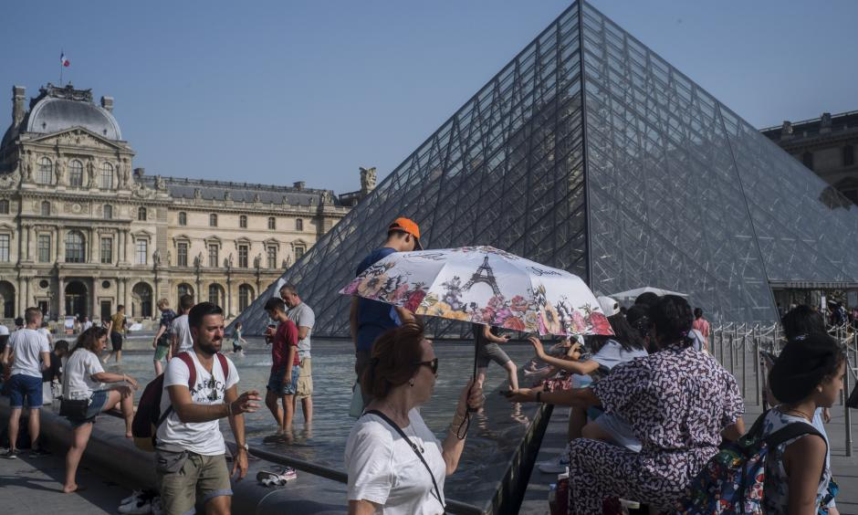 People cool off next to the fountains at Louvre Museum in Paris, France, Wednesday, July 24, 2019. Temperatures in Paris are forecast to reach 41 degrees C (86 F), on Thursday. Credit: Rafael Yaghobzadeh, AP