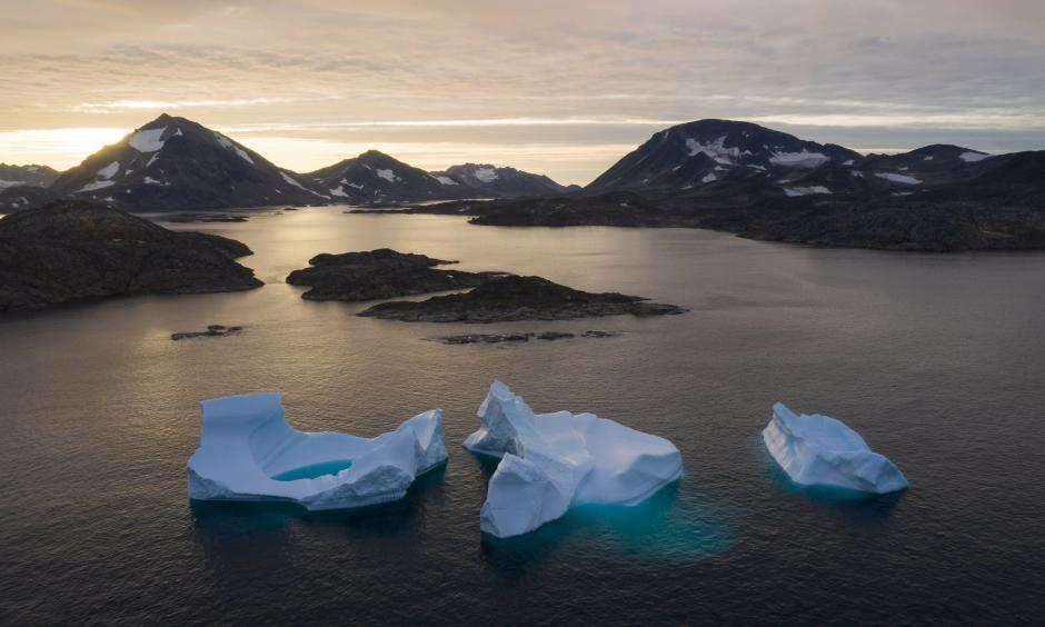 In this August 16, 2019 photo, large icebergs float away as the sun rises near Kulusuk, Greenland. Scientists are hard at work trying to understand the rapid melting of the ice. Credit: Felipe Dana, AP