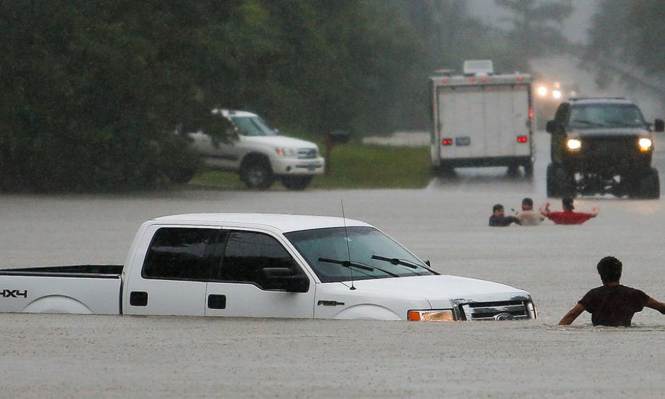 The three men in the foreground had to abandon their truck Friday after getting caught in rising flood waters in Magnolia, Tex. Photo: Michael Ciaglo, Houston Chronicle, via Associated Press
