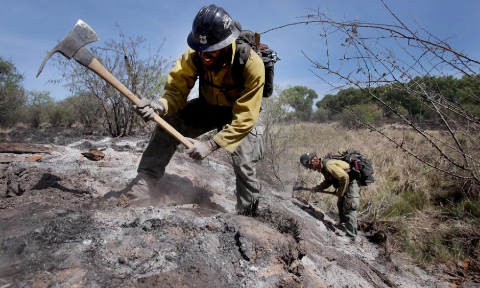 Mike Trubman, left, works with fellow Black Mesa Type-1 Interagency Hotshot Crew member Steve Daly, right, to mop up hot spots along Cienega Creek east of Empire Ranch while the Sawmill Fire burns on April 27, 2017, burning in Southeastern Arizona between Green Valley and J-6. Photo: Mike Christy, Arizona Daily Star
