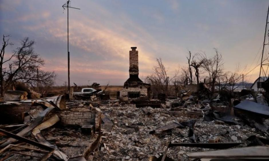 A chimney is all that stands in the footprint of a home destroyed by wildfires near Laverne, Okla., on March 12, 2017. Credit: Lucas Jackson, Reuters