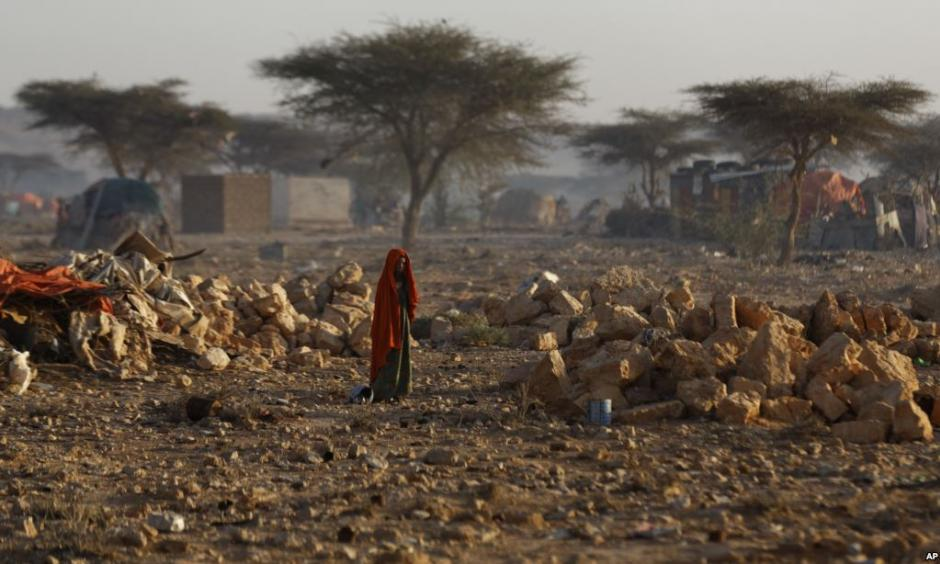 A Somali woman walks through a camp of people displaced from their homes elsewhere in the country by the drought, shortly after dawn in Qardho, Somalia, March 9, 2017. Photo: AP