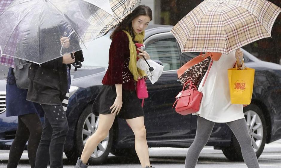 Pedestrians make their way through a street in Tokyo while a powerful typhoon approaches Tokyo, Oct. 6, 2014. Photo: AP/Kyodo News