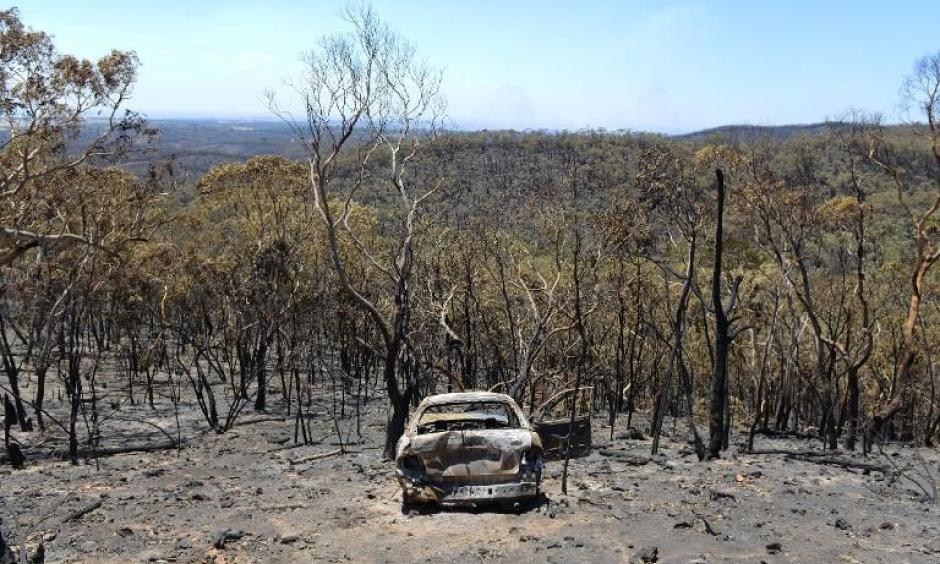 A charred car stands destroyed after a bushfire moved through the area near One Tree Hill in the Adelaide Hills. Photo: Yahoo News