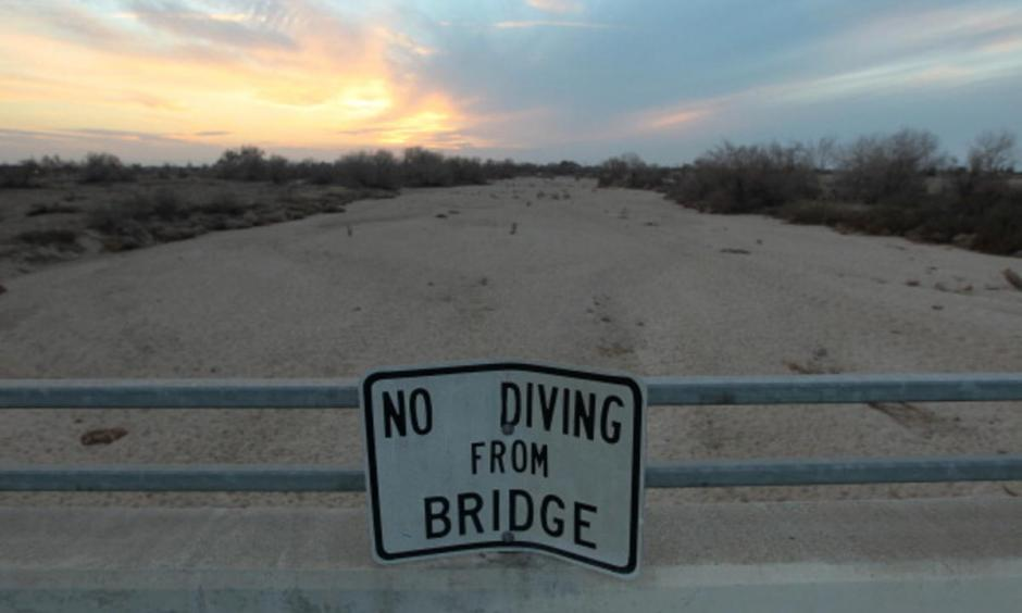A sign from wetter times warns people not to dive from a bridge over the Kern River, which has been dried up by water diversion projects and little rain, on February 4, 2014 in Bakersfield, California. Photo: Associated Press
