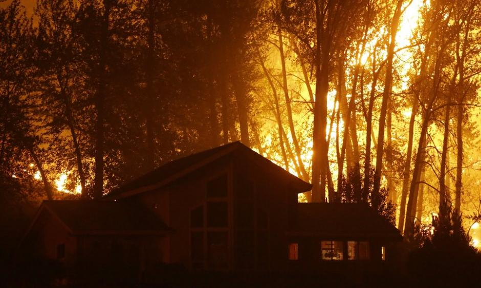 A wildfire burns behind a home in Twisp, Washington, in August 2015. Photo: Ted S. Warren, AP