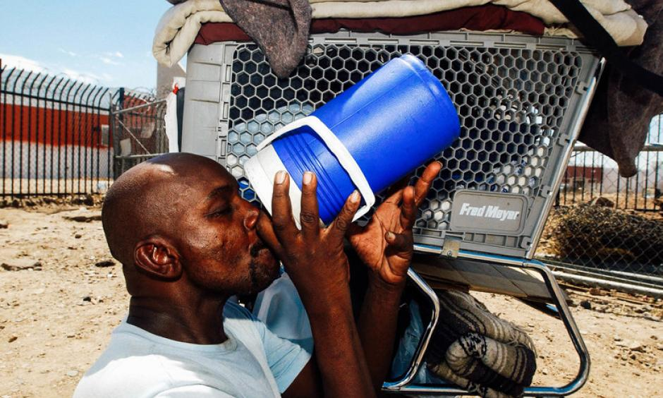 Desmont Smith sits in the shade of his shopping cart drinking water in Phoenix. Credit: Ann Johansson, Corbis via Getty Images