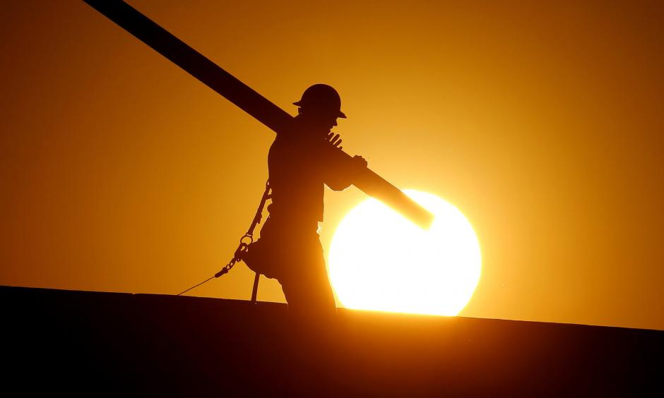 A home builder works at sunrise on Monday in Gilbert, Arizona, in an effort to beat the rising temperatures. Photo: AP