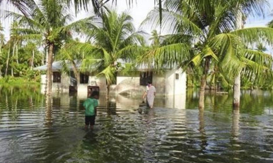 A woman and a child walk through knee-deep water to reach their home during a king tide event on Kili in the Marshall Islands in January 2015. Photo: Bikini Atoll Local Government / Associated Press