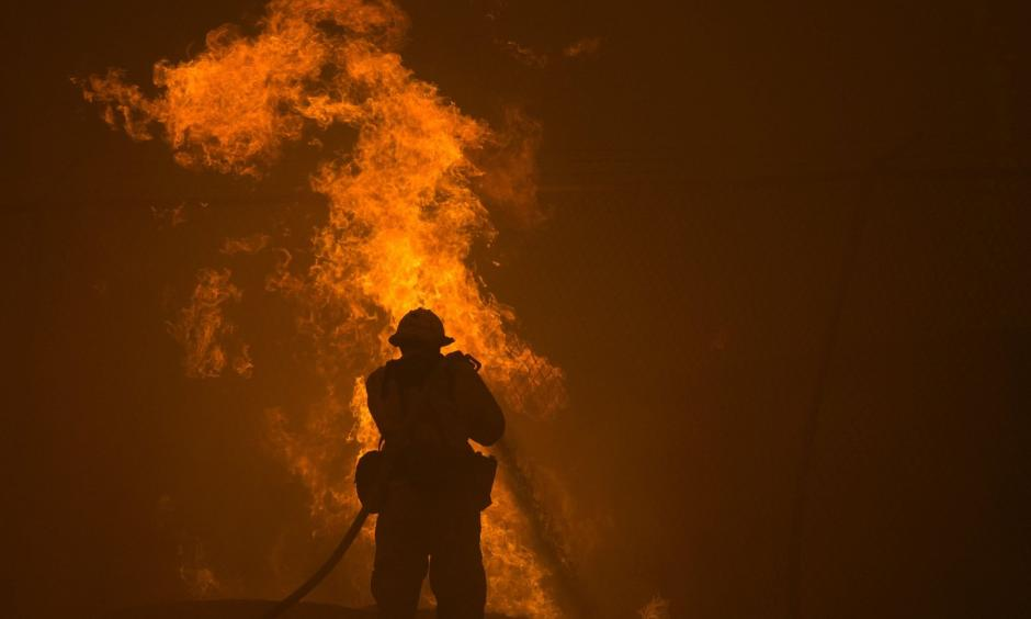 A firefighter hoses down burning pipes near a water tank. Photo: David McNew/Getty Images