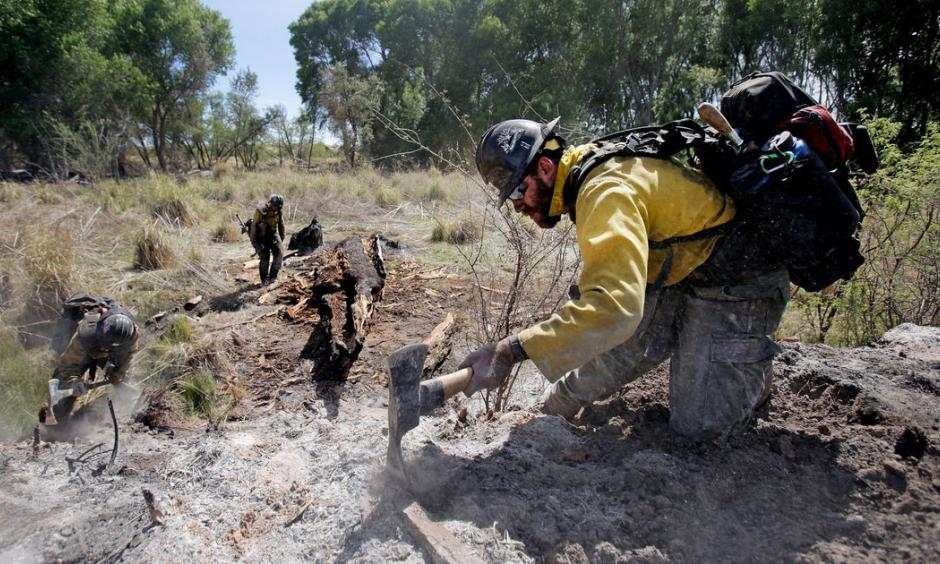 Mike Trubman, right, works with fellow Black Mesa Type-1 Interagency Hotshot Crew members Steve Daly, left, and Sean Hosier to mop up hot spots along Cienega Creek east of Empire Ranch while the Sawmill Fire burns on April 27, 2017, burning in Southeastern Arizona between Green Valley and J-6. Photo: Mike Christy, Arizona Daily Star