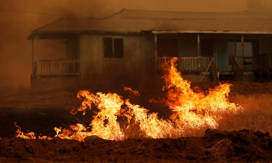 Grass burns in front of a home during the Detwiler fire in California, on July 19. Photo: Stephen Lam, Reuters