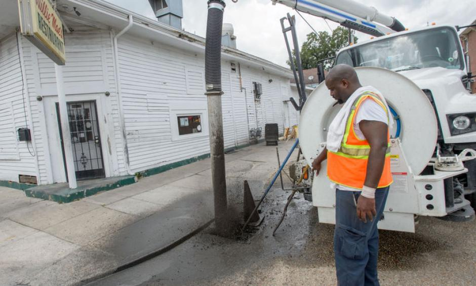 A New Orleans city worker sprays out mud and debris from a storm drain at Wille Mae's Restaurant before the governor toured it and other businesses damaged by Saturday's flash flooding in New Orleans, La. Monday, Aug. 7, 2017. Photo: Matthew Hinton