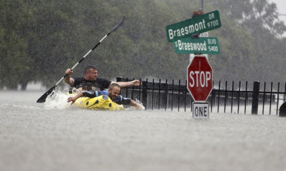 Two kayakers try to beat the current pushing them down an overflowing Brays Bayou from Tropical Storm Harvey in Houston, Texas, Sunday, Aug. 27, 2017. Photo: Mark Mulligan/Houston Chronicle via AP